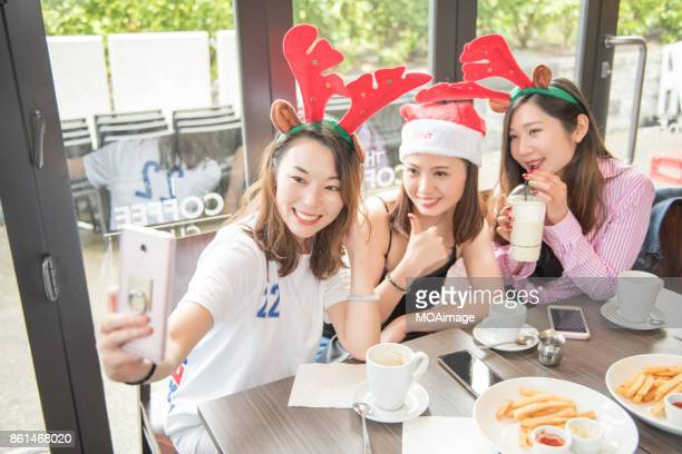 Summer Christmas-group of young ladies having a party at cafe shop and taking self-portrait