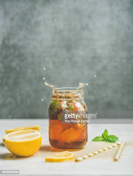 Summer cold Iced tea with fresh bergamot, mint and lemon in glass jar with splashes on light table, grey concrete wall at background