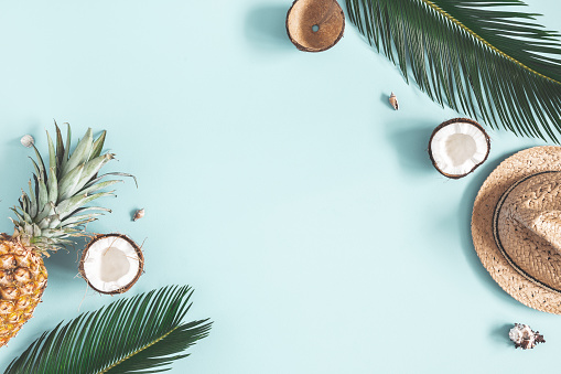 Summer composition. Tropical palm leaves, hat, fruits on blue background. Summer concept. Flat lay, top view, copy space 1149086724