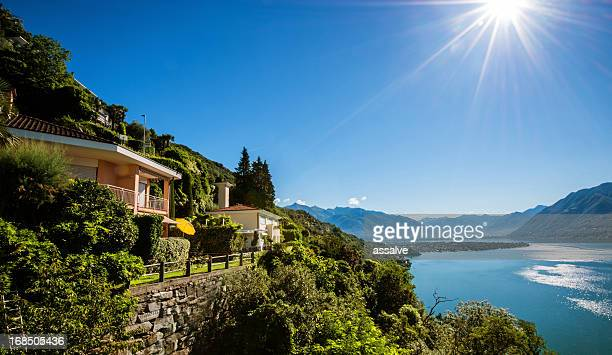 summer cottages on a cliff at lake maggiore in switzerland - locarno stock photos and pictures