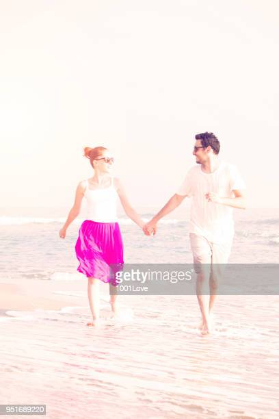 Summer couple running at sunset on beach. Freedom concept.