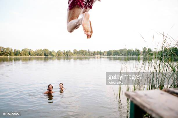 Summer day: three young adults jump from jetty into lake