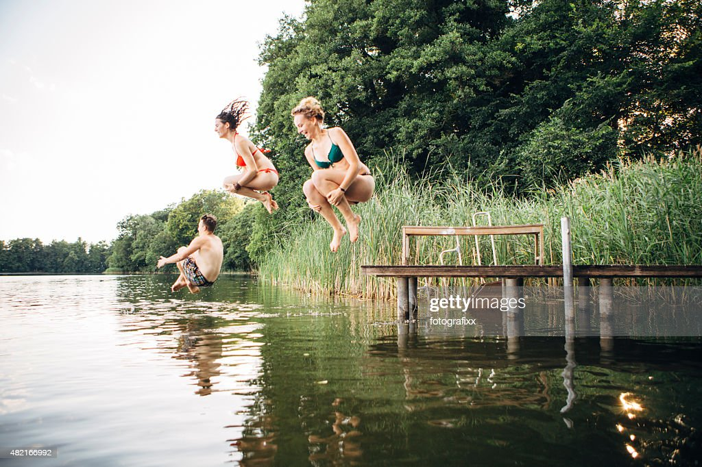 summer day: three young adults jump from jetty into lake : Stock Photo