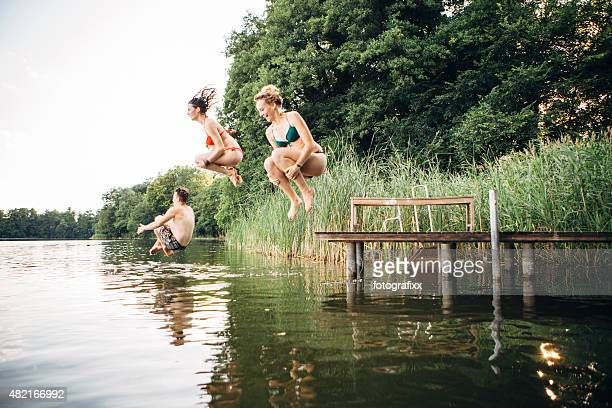 summer day: three young adults jump from jetty into lake - lake stock pictures, royalty-free photos & images