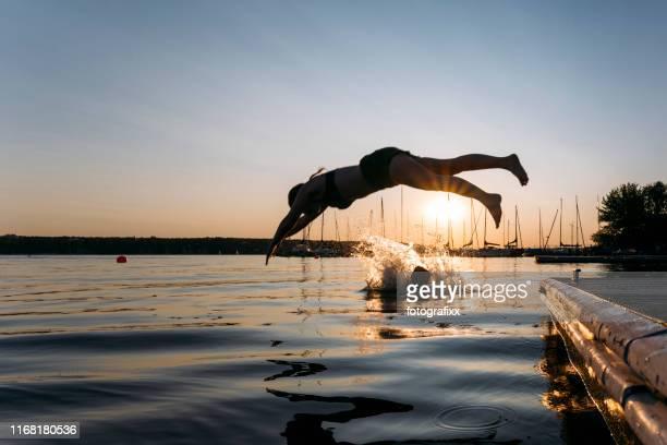 sommertag: junge frau springt bei sonnenuntergang vom steg in den see - see stock-fotos und bilder