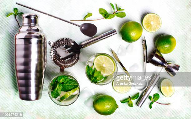 summer drink mojito ingredients - white rum, lime, mint, and ice, and set of bar tools for making a cocktails arranged on a stone background. - kombination stock-fotos und bilder