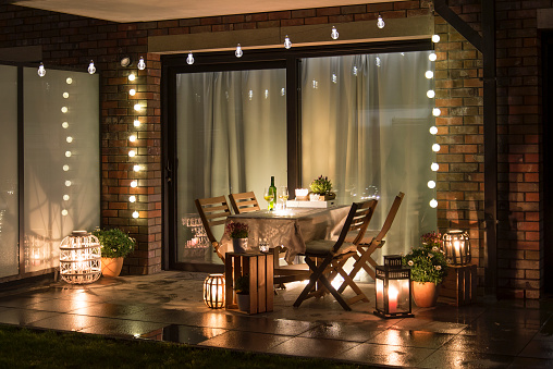 Summer evenig terrace with candles, wine and lights 1135183699