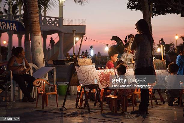 CONTENT] A summer evening along the Malecon in La Paz Mexico Children doing art in the plaza