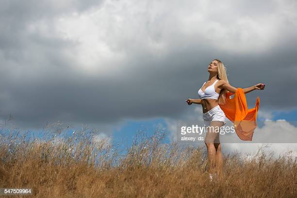 summer freedom. young woman sunbathing at dry meadow - belly ring stock photos and pictures