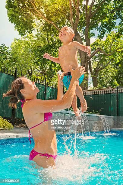 Sommerspaß für Mutter und Sohn in den pool im Hof.