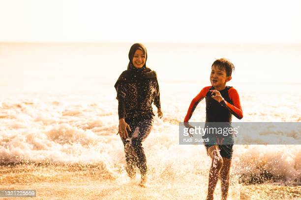 summer fun on the bali beach - religious dress stock pictures, royalty-free photos & images