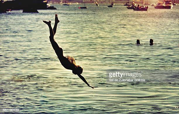 Summer! Girl jumping headfirst into the sea.