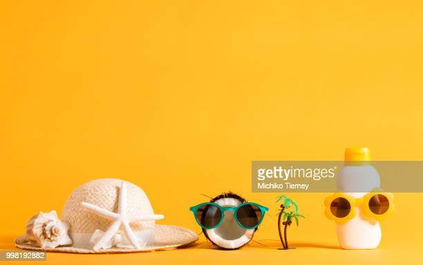 Summer hat, coconut and sunblock wearing sunglasses