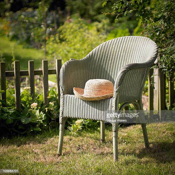 Summer hat on chair in garden.
