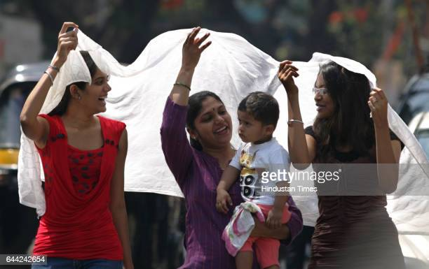Summer Heat Mother and Child Three women try a dupatta as a shade for a child to beat the heat at Andheri