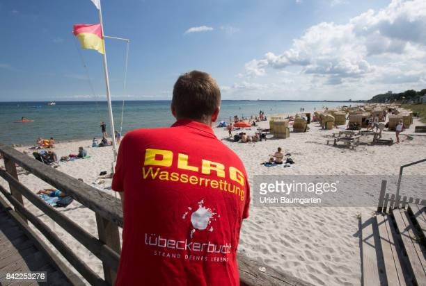 Summer holidays and beach holidays in Scharbeutz at the Baltic Sea. Employee of the Water Rescue Service on observation post.