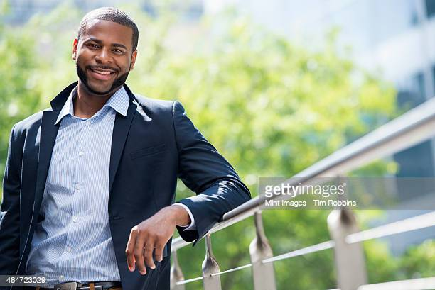 summer in the city. businesspeople outdoors, on the go. a man in a blue jacket and open necked shirt.  - sideburn stock pictures, royalty-free photos & images