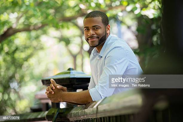 summer in the city. businesspeople outdoors, on the go. a man in a white shirt leaning on a railing.  - sideburn stock pictures, royalty-free photos & images
