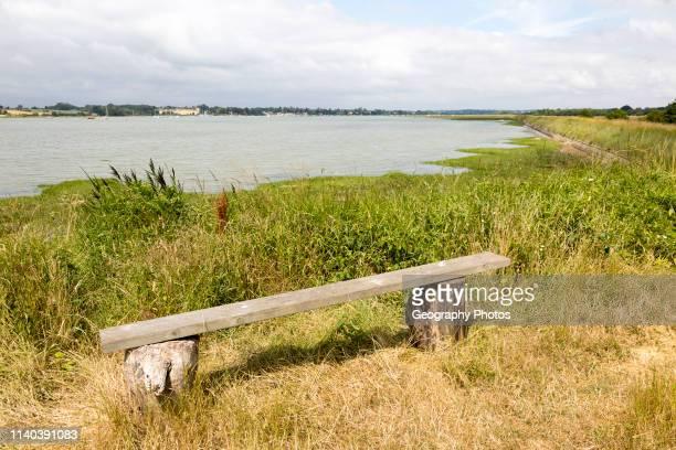 Summer landscape view of bench overlooking River Deben tidal estuary Sutton Suffolk England UK