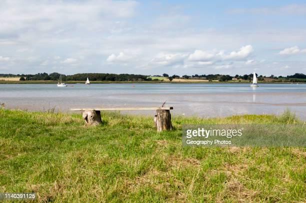 Summer landscape view of bench overlooking sailing boats on River Deben estuary Sutton Suffolk England UK