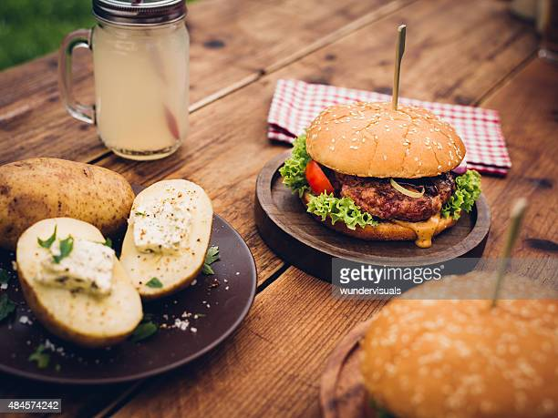 Summer meal of burgers and baked potatoes with a drink