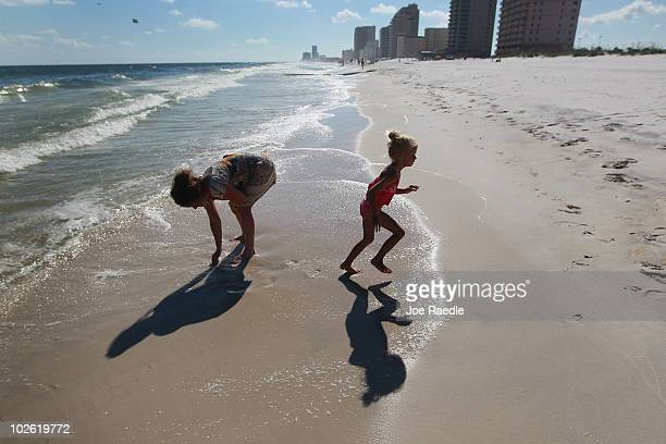 Summer Miller and her mother Tammy James walk along a beach which was not as busy as last year as people stayed away due to the threat of...