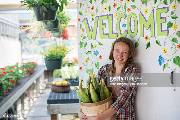 Summer on an organic farm. A girl holding a basket of fresh corn standing by the Welcome sign.