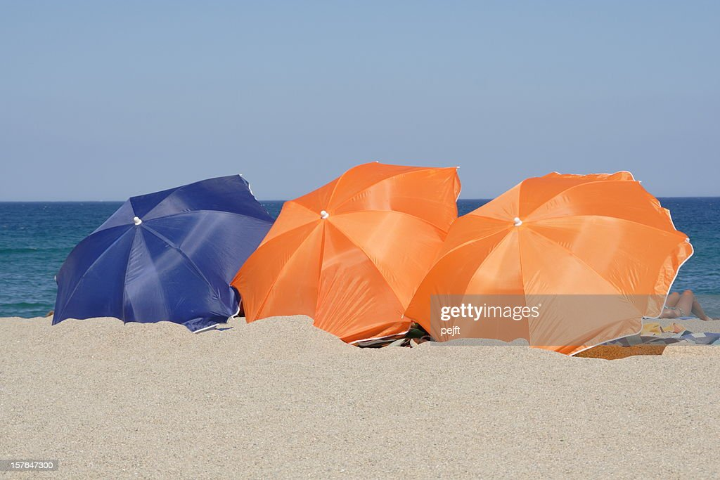 Summer on the beach - Orange and blue parasol : Stock Photo