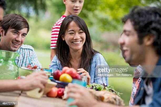 A summer party outdoors. Adults and children around a table.