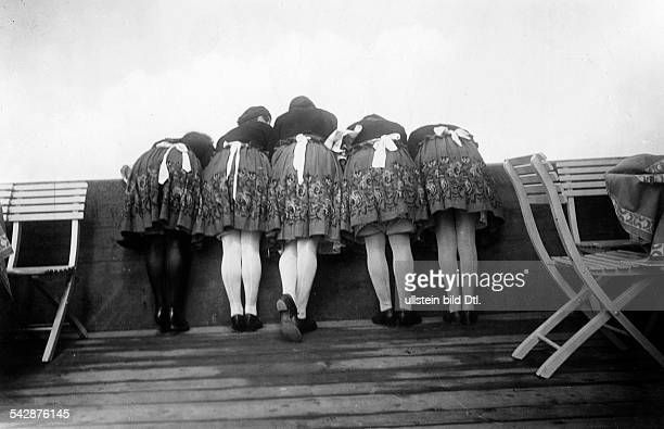 Summer pictures Back view of five women in skirts bending over a wall and watching downwards - 1930 - Vintage property of ullstein bild