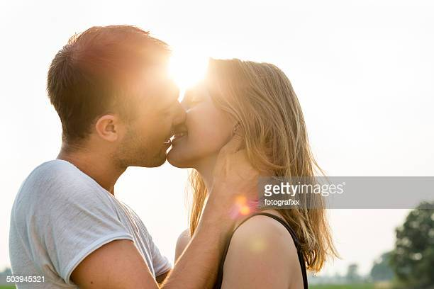 summer portrait of a kissing young adult couple, back lit - kiss stockfoto's en -beelden
