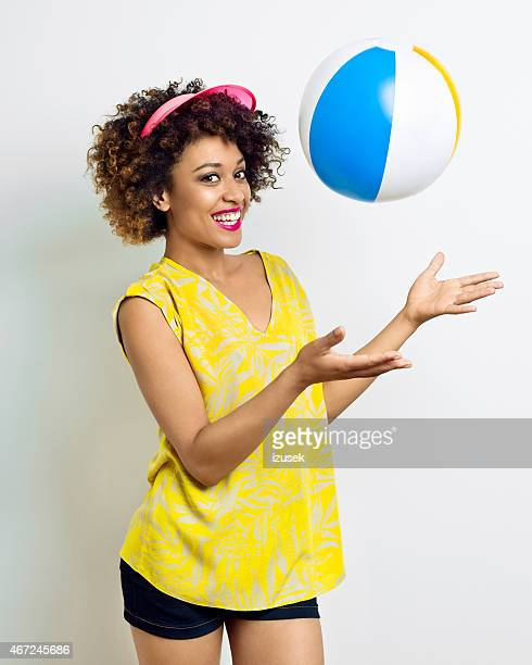 Summer portrait of afro american girl playing beachball