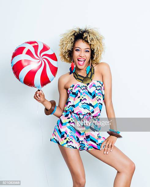 Summer portrait of excited afro young woman with balloon