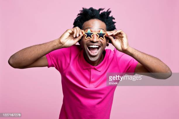 summer portrait of excited young man wearing star shaped sunglasses - star shape stock pictures, royalty-free photos & images