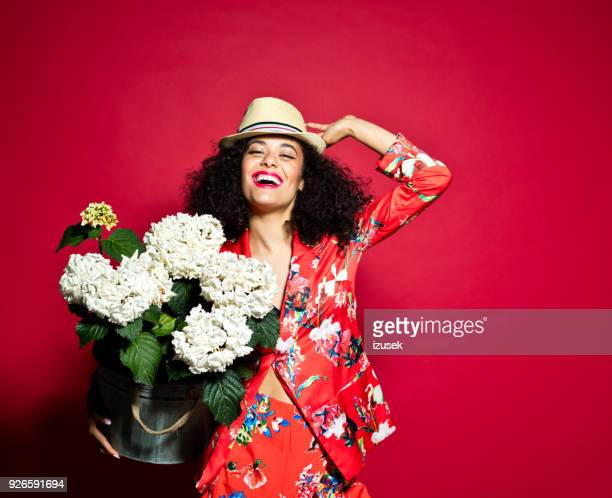 Summer portrait of excited young woman with flowers against red background