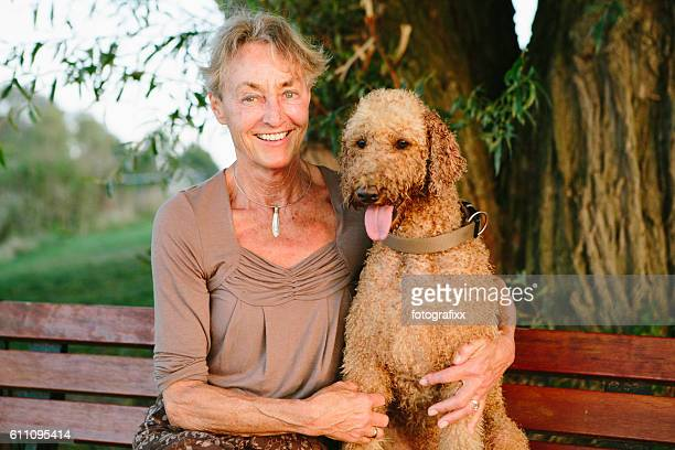 summer portrait: senior woman with her dog (labradoodle), arms around - labradoodle stock photos and pictures