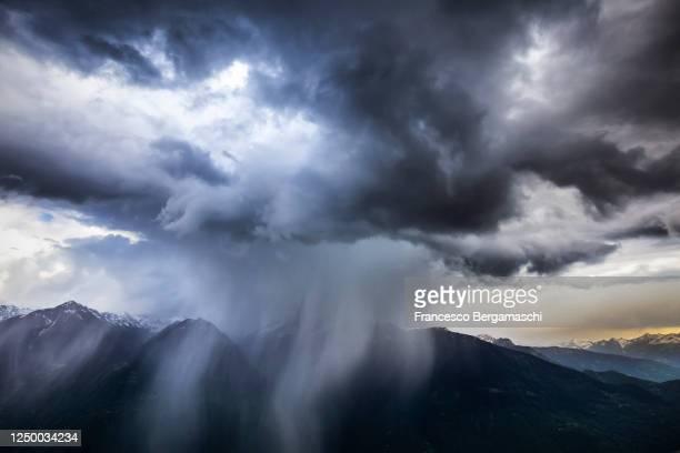 summer rainstorm at sunset in the alps. - italia stock-fotos und bilder