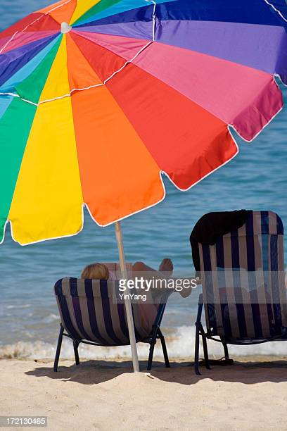 Summer Reading Under Sunshade of Beach Umbrella in Tropical Location