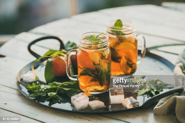 Summer refreshing cold peach ice tea with fresh mint in glass jars on metal tray over wooden garden table