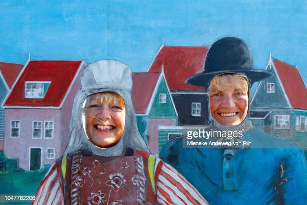 Summer season in Marken, North Holland and tourists pose for fun in a frame with cut-out faces