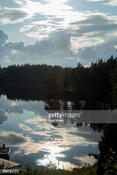 summer sky mirroring in swedish lake - dalsland stock photos and pictures