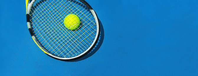 Summer sport concept with tennis ball and racket on blue hard tennis court. 1153628111