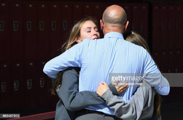 Summer Stadtlander left and Marie Langer right are hugged by high school principal Scott Fogo center at Faith Lutheran Middle School and High School...
