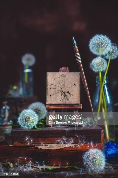 Summer still life with a little dandelion painting on an easel, ink pen and, stack of wooden boxes