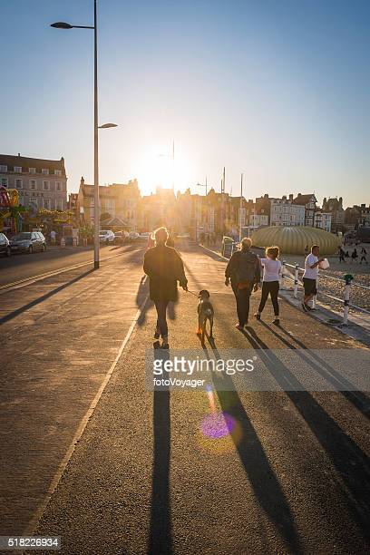 Summer sunset holidays seaside tourists walking along promenade Weymouth Dorset