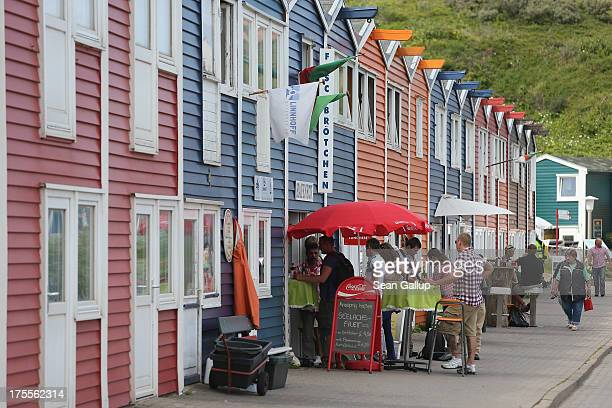 Summer tourists stop for a snack among a row of houses built after World War II in Helgoland town on August 3 2013 on Heligoland Island Germany...