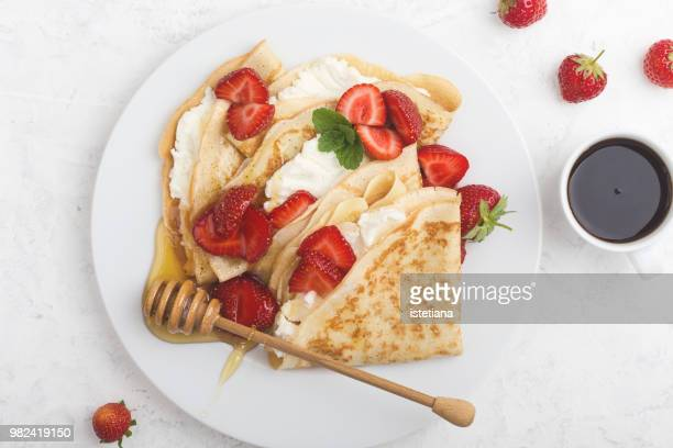 Summer treat, healthy breakfast with crepes, fresh strawberry, cheese and coffee