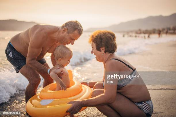 summer vacation at sea, grandparents with grandson - sea swimming stock pictures, royalty-free photos & images