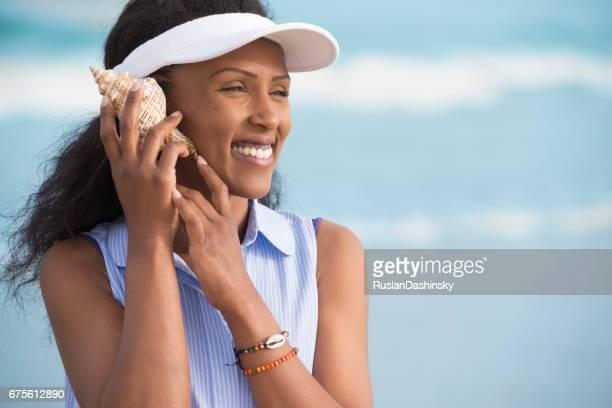 Summer vacation woman enjoying to listen the sea sound.