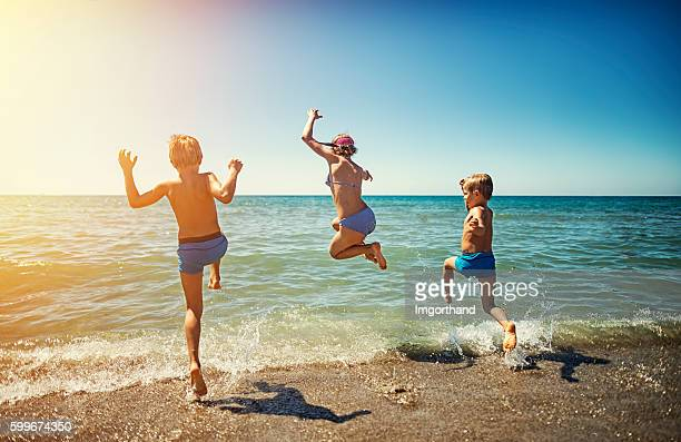 Summer vacations in Italy - kids jumping into the sea